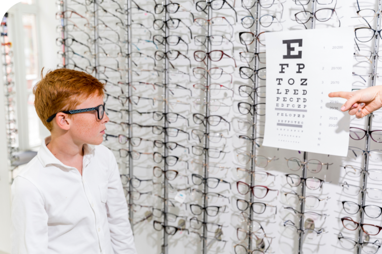 cute-boy-looking-snellen-chart-optics-clinic 1
